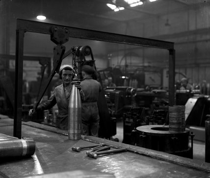 Works photographic negative of female employee loading a 6in. shell onto the bending press
