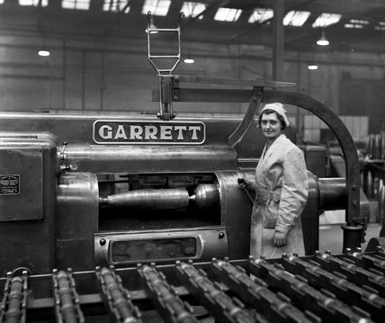 Works photographic negative of female employee with a 6in. shell in position on the finish turning machine
