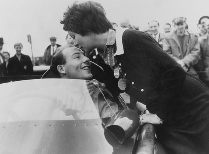 Stirling Moss, in car, kisses his fiance Katie Molson at Brands Hatch, 1957