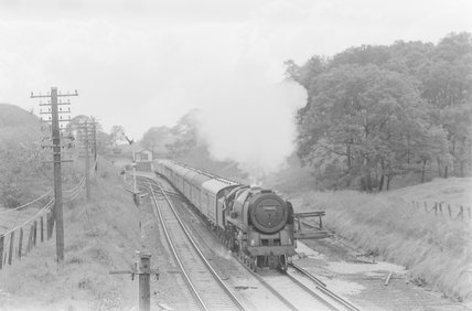 A steam locomotive hauling a goods train passing a siding. Locomotive number: 70013,A1969.70/Box 5/Neg 1235/26
