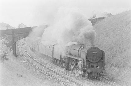 A steam locomotive pulling a passenger train, passing under bridge. Locomotive number: 70042,A1969.70/Box 5/Neg 1235/27