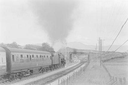 A steam locomotive pulling a passenger train, approaching a bridge,A1969.70/Box 5/Neg 1236/29