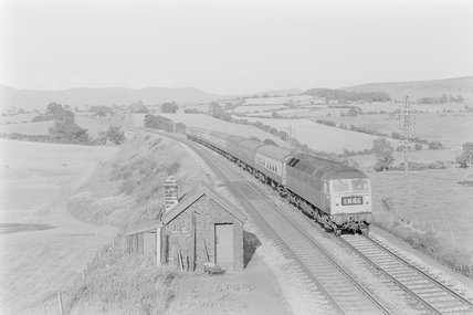 A diesel locomotive pulling passenger train 1M46 on an embankment. Locomotive number: 1M46,A1969.70/Box 5/Neg 1236/31