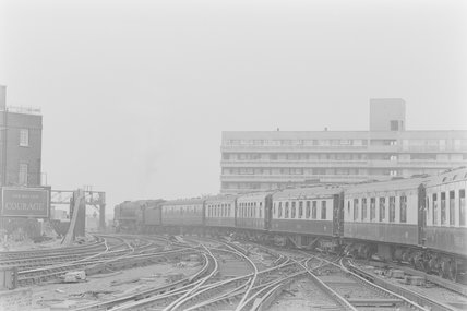 A steam locomotive pulling a passenger train, leaving a station,A1969.70/Box 5/Neg 1238/3