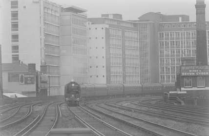 A steam locomotive pulling a passenger train, entering a station,A1969.70/Box 5/Neg 1238/4