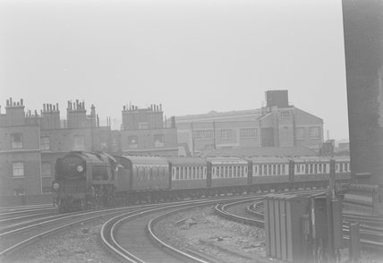 A steam locomotive pulling a passenger train, entering a station,A1969.70/Box 5/Neg 1238/6