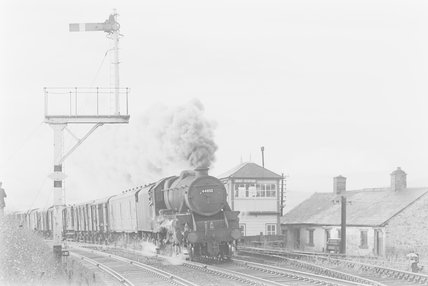 A steam locomotive hauling a goods train, passing a signal box,A1969.70/Box 5/Neg 1240/12