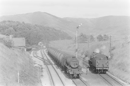 A steam locomotive hauling a goods train, passing a steam locomotive on a parallel track,A1969.70/Box 5/Neg 1241/31