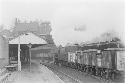 A steam locomotive hauling a goods train through a station,A1969.70/Box 5/Neg 1249/15