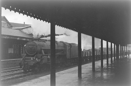 A steam locomotive hauling a goods train through a station,A1969.70/Box 5/Neg 1249/16
