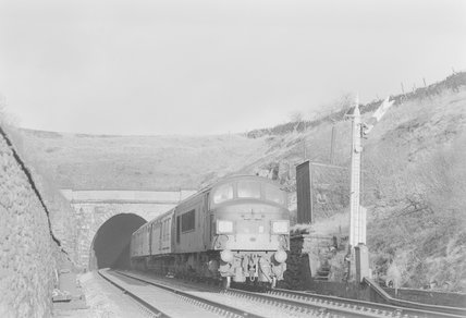 A diesel locomotive pulling a passenger train, emerging from a tunnel,A1969.70/Box 5/Neg 1254/14