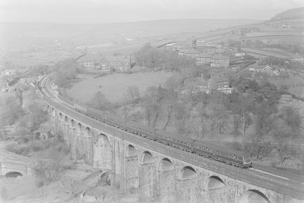A diesel locomotive pulling a passenger train across a viaduct, view from above,A1969.70/Box 5/Neg 1256/34
