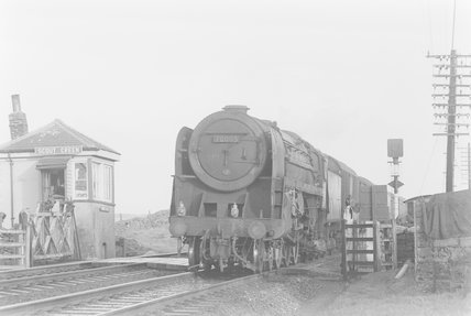 A steam locomotive pulling a passenger train, passing a signal box,A1969.70/Box 5/Neg 1257/12