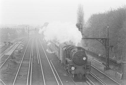 A steam locomotive pulling a passenger train, on a third-rail track,A1969.70/Box 5/Neg 1258/31