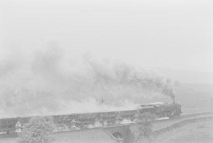 A steam locomotive hauling a goods train, passing over a bridge between fields,A1969.70/Box 5/Neg 1261/4