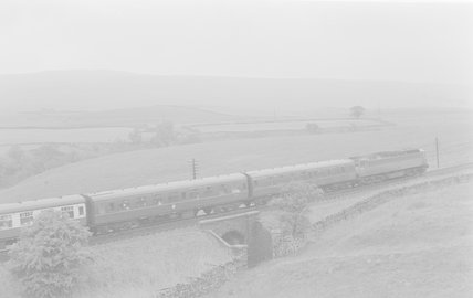 A diesel locomotive pulling a passenger train, passing over a bridge between fields,A1969.70/Box 5/Neg 1261/7
