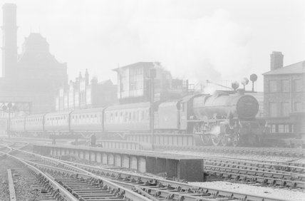 A steam locomotive pulling a passenger train, entering an urban station,A1969.70/Box 5/Neg 1262/4