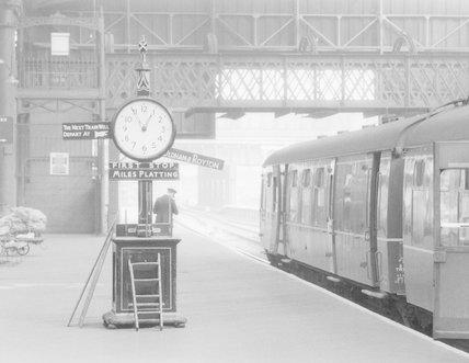 A passenger train at a platform, alongside a departure board,A1969.70/Box 5/Neg 1262/8