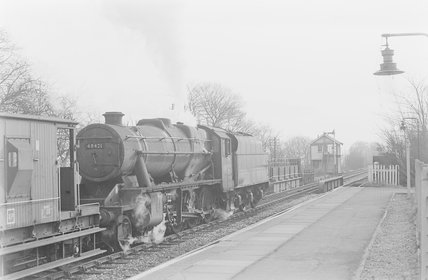 A steam locomotive passing through a station,A1969.70/Box 5/Neg 1263/28