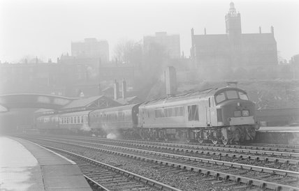 A diesel locomotive pulling a passenger train, departing station,A1969.70/Box 5/Neg 1265/22