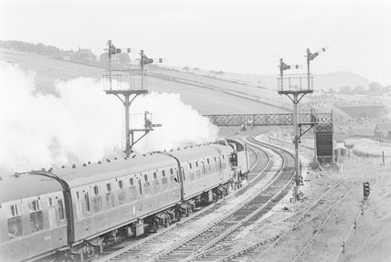 A steam locomotive shunting a passenger train past signal gantries and a bridge,A1969.70/Box 5/Neg 1267/5