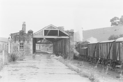 A steam locomotive hauling a goods train, passing a disused station,A1969.70/Box 5/Neg 1268/10