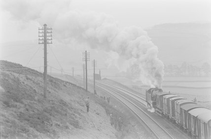 A steam locomotive at the rear of a goods train, with trainspotters on a hillside.,A1969.70/Box 5/Neg 1271/8