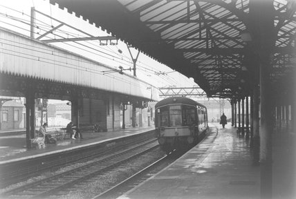 A diesel locomotive with a passenger train at a platform. ,A1969.70/Box 5/Neg 1273/9