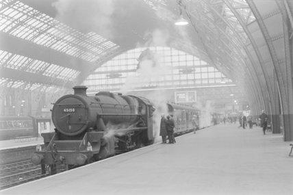 A steam locomotive with a passenger train at a platform. ,A1969.70/Box 5/Neg 1274/20