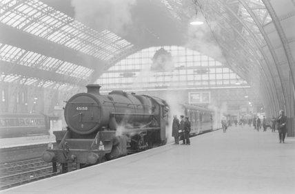 A steam locomotive with a passenger train at a platform . ,A1969.70/Box 5/Neg 1274/21