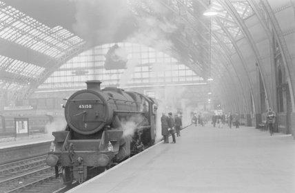 A steam locomotive with a passenger train at a platform. ,A1969.70/Box 5/Neg 1274/22