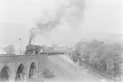 A steam locomotive hauling a goods train, approaching a viaduct.  ,A1969.70/Box 5/Neg 1276/12