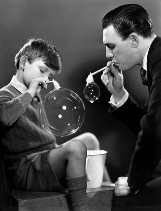 Father and son blowing bubbles, c 1948.