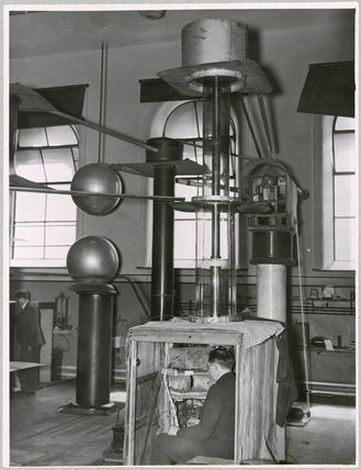 Dr. Ernest Thomas Sinton Walton in the cabin of Cockcroft and Walton's apparatus at Cambridge in 1932