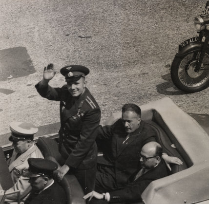 Crowds applaud as Yuri Gagarin leaves London airport in a Rolls Royce convertible.