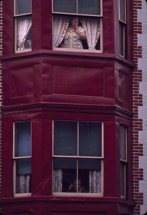 Woman at window, parade, USA. 1965