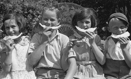 Four children eating slices of melon, c 1920s