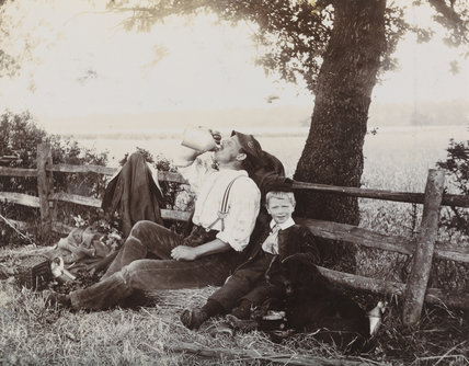 Man, boy and dog resting against a fence, taken in about 1896.