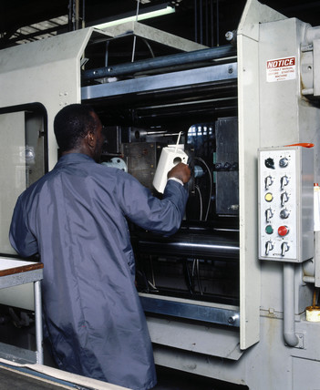 Removing plastic kettle body from an injection moulding machine, c 1985.