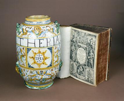 Albarello drug jar, Italian, 1641, and a copy of 'Gerarde's Herball', 1633.