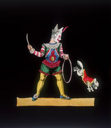 A circus clown with a dog jumping through a hoop, 19th century.