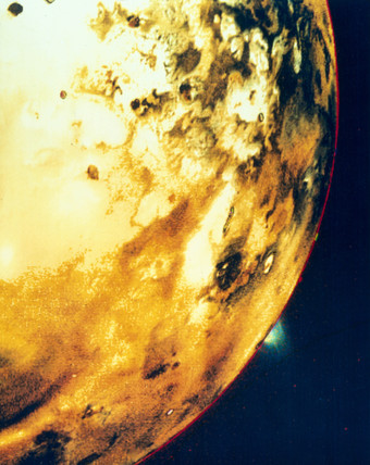 Io, one of the moons of Jupiter, showing a volcanic eruption on the horizon, 1979.