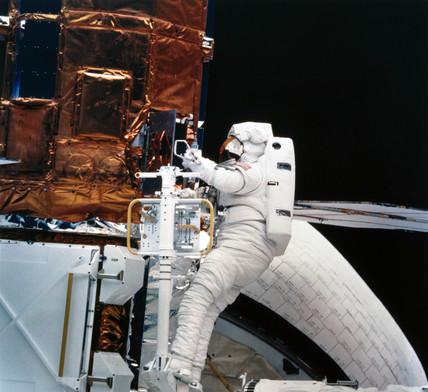Shuttle astronaut with Solar Maximum Satellite, 1984.