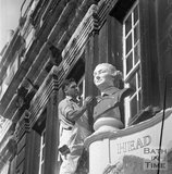 Restoring the stone head of David Garrick above the Garrick's Head, Bath, 16 September 1970