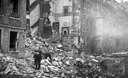 A man looks though the rubble in New King Street, Bath, 1942