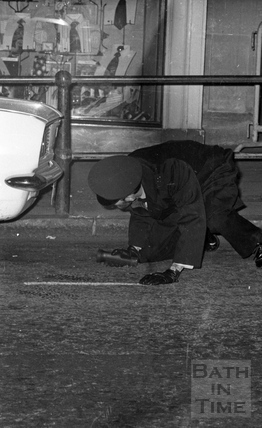 A policeman searching under a car, High Street 1974