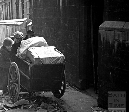 An elderly couple are helped moving their possessions along Bridewell Lane, April 1942