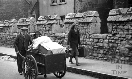 An elderly couple are helped moving their possessions along Upper Borough Walls, Bath, April 1942