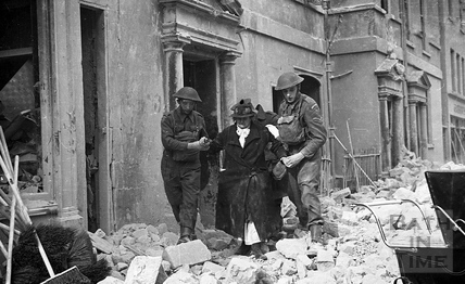 An elderly lady is helped from her house after the bombings in Bath, April 1942