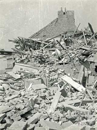 A child's cot amongst the rubble of a destroyed home in Bath, April 1942